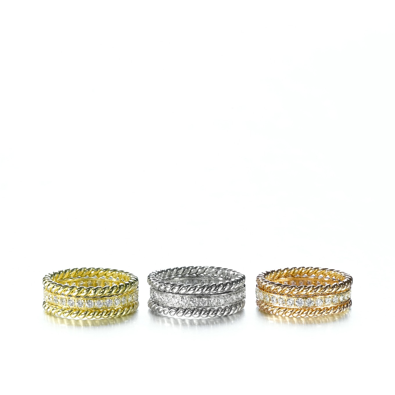 A CLASSIC TRIO OF BRAIDED & DIAMOND ETERNITY BANDS IN YELLOW, WHITE, & ROSE GOLD