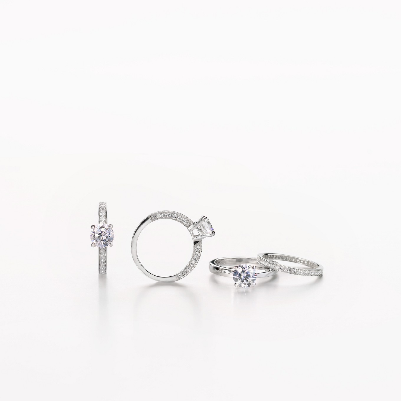 CLASSIC SOLITAIRE RINGS FROM LEFT: SOLITAIRE WITH PARTIAL DIAMOND BAND, SOLITAIRE WITH FULL DIAMOND BAND, SOLITAIRE WITH PLAIN BAND, MINI DIAMOND ETERNITY BAND