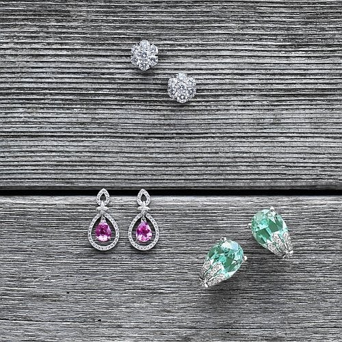 "From top: ""Snowflake"" diamond cluster earrings in white gold. ""Olivia"" pink saphire & diamond earrings with sevilla motif in white gold. ""Sophie"" 19.53 ct oval green tourmaline & diamond earrings in white gold"